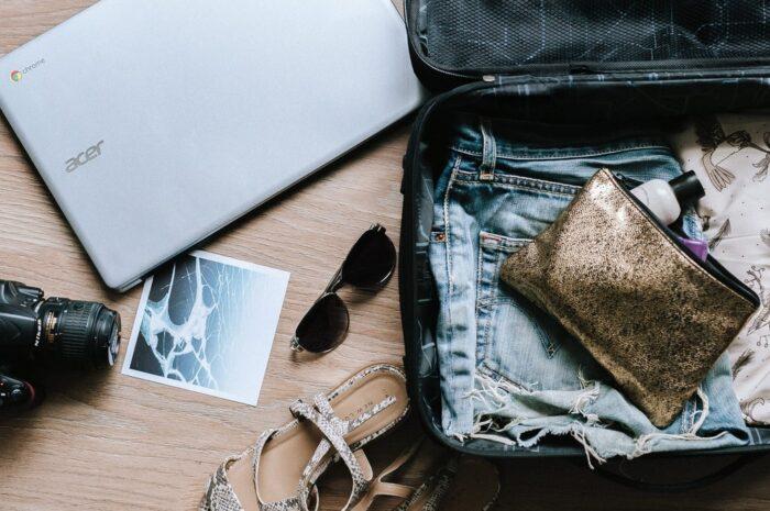 Otevřený cestovní kufr s několik věcmi pro cestování.