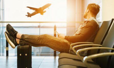 Mladík vyhlíží let a ví, že má kvalitní cestovní pojištění.