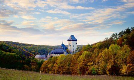 Státní hrad Karlštejn mezi vzrostlými stromy.