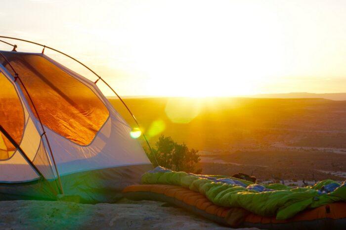 Spacák rozložený vedle stanu s krásným východem slunce.